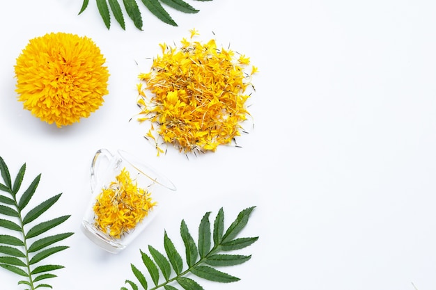 A glass cup with marigold flower petals on white background. flower herbal tea concept. copy space