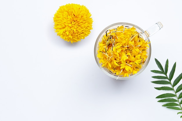 A glass cup with marigold flower petals on white background. flower herbal tea concept.