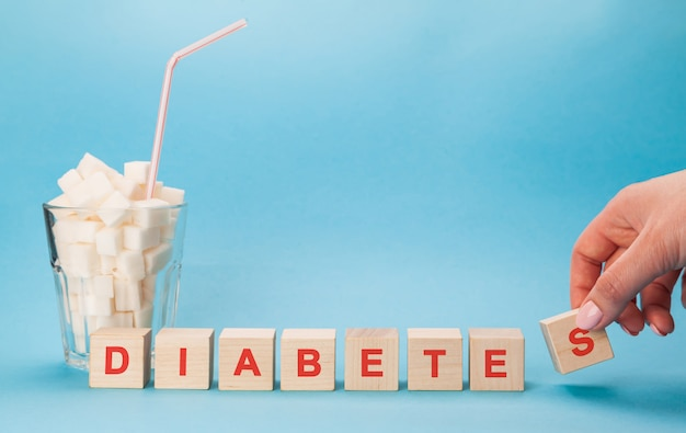 Glass cup with a straw full of cubes of white sugar. block letters of diabetes in a crossword puzzle.