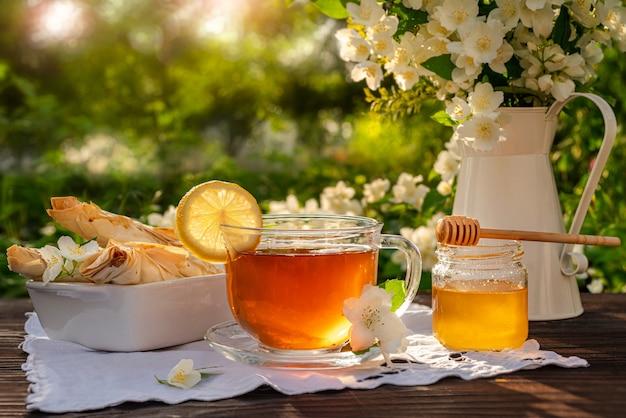차와 레몬 꿀 디퍼 페이스트리 크로와상 금속 주전자와 부케 자스민이 든 유리 컵