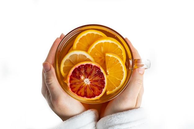 女性の手に赤と黄色のオレンジからお茶とガラスのカップ、上面図、白で隔離