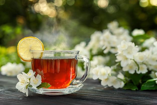 Стеклянная чашка с чаем, лимоном, ветками жасмина на деревянном столе. на природе, пикник, поздний завтрак.