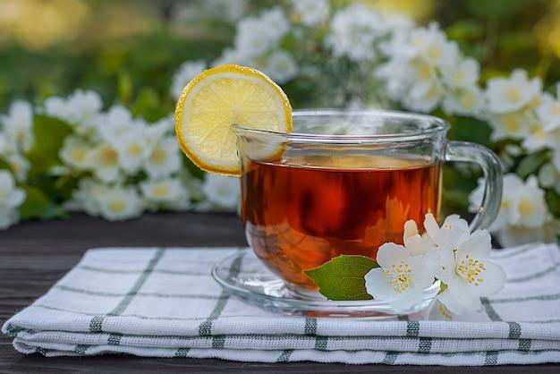 Стеклянная чашка с чаем, лимонная салфетка, ветки жасмина на деревянном столе
