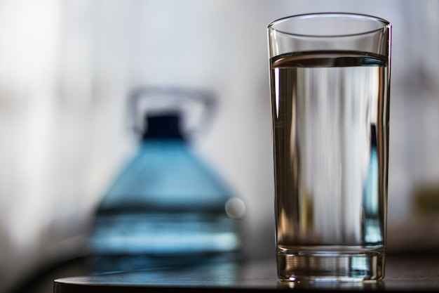 Glass cup with water and a plastic bottle