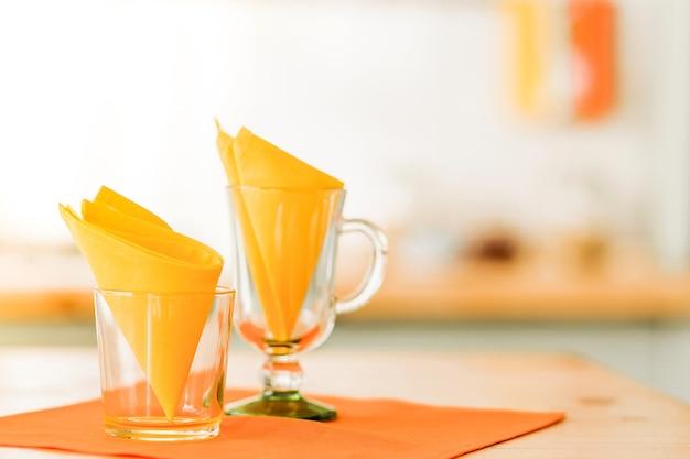 노란색 냅킨으로 장식 된 유리 컵은 주황색 냅킨에 테이블 위에 서 있습니다. 방에 햇빛