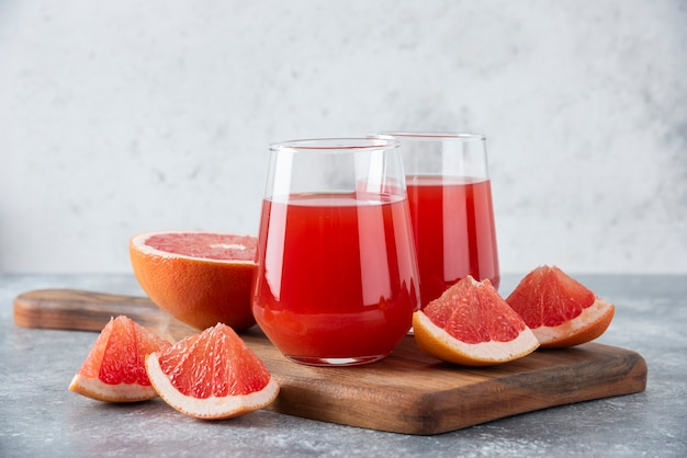 Glass cups of fresh grapefruit juice with slices of fruits placed on wooden board .