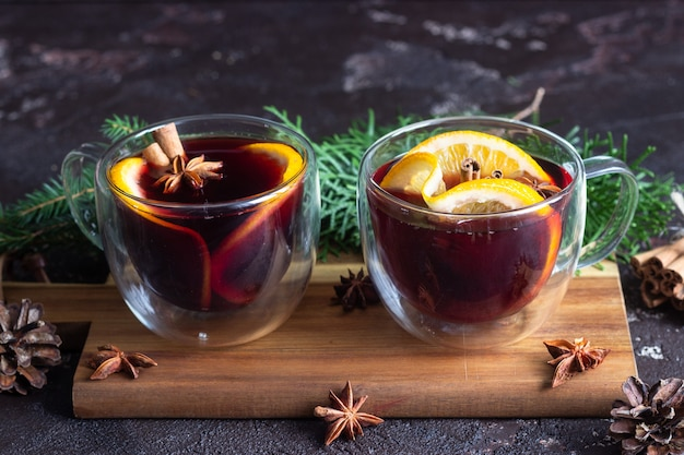 Glass cups of hot mulled wine or gluhwein with spices and orange pieces.
