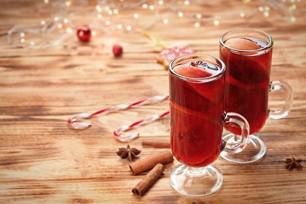 木製の背景においしいクリスマスグリューワインのガラスカップ
