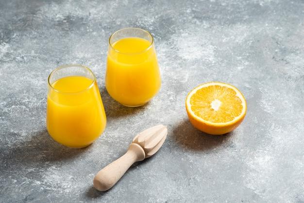 オレンジジュースのガラスカップと木製のリーマー。