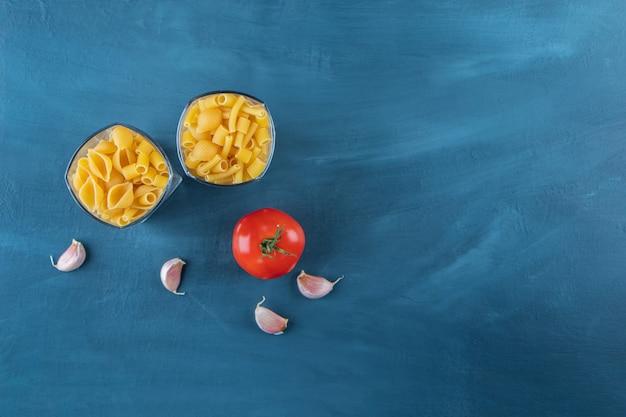 新鮮な赤いトマトとニンニクの生パスタのガラスカップ。