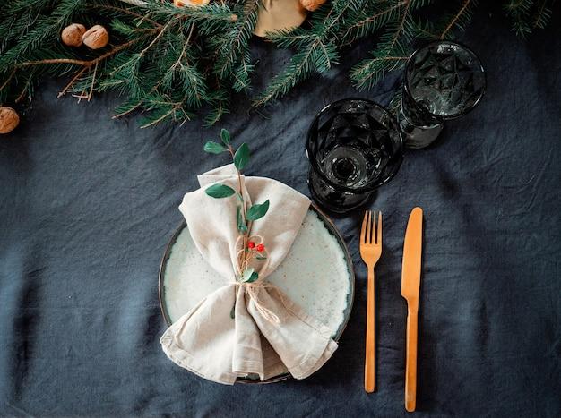 クリスマスのプレートとモミの横にあるテーブルの上のガラスカップ