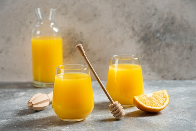 A glass cups of orange juice and a wooden dipper.