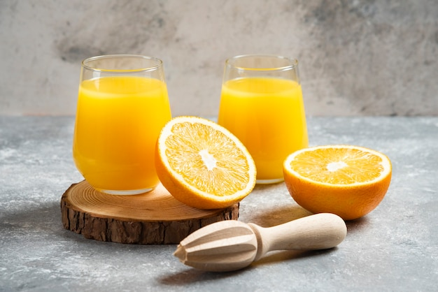 Glass cups of orange juice and a wooden reamer .