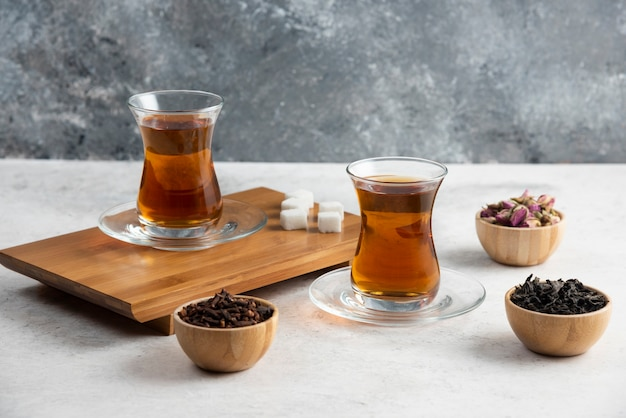 Glass cups of tea with sugar on wooden board.