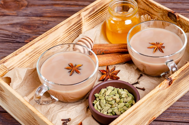 Glass cups of traditional indian chai masala tea on a tray with ingredients.