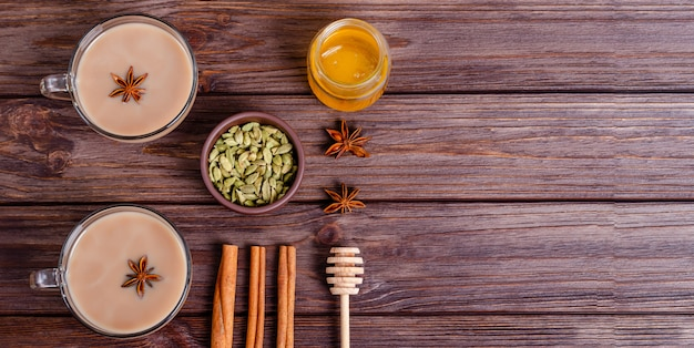 Glass cups of traditional indian chai masala tea on a tray with ingredients