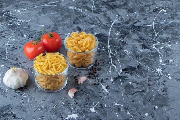 Bicchieri di vetro di pasta cruda con due pomodori freschi e aglio su uno sfondo di marmo.