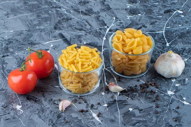 Bicchieri di vetro di pasta cruda con due pomodori freschi e aglio su una superficie di marmo.