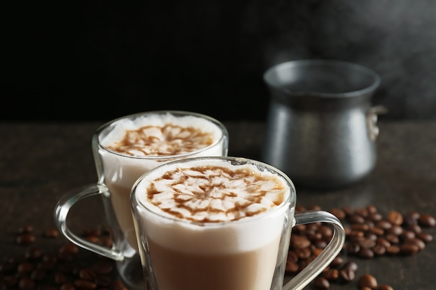 Glass cups with latte macchiato on table