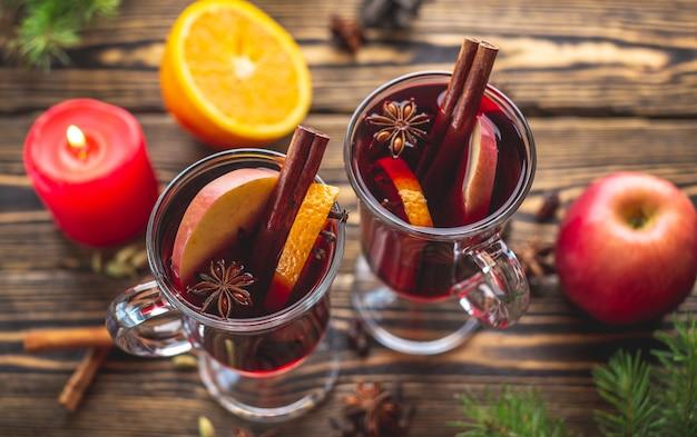 シナモン、アニス、フルーツで飾られたグリューワインのガラスカップ