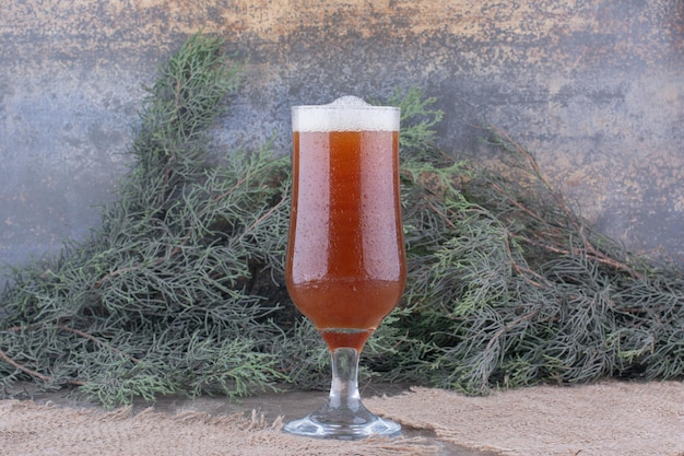 Glass of dark beer on burlap with pine branch. high quality photo