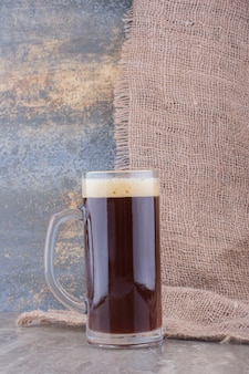 Glass of dark beer on marble table. high quality photo