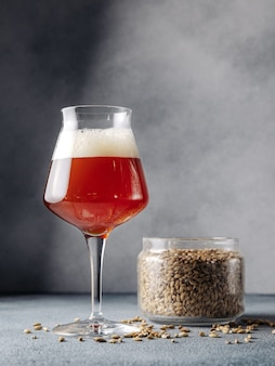 A glass of dark beer stands next to a can of malt. grey background