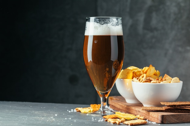 Glass of dark beer with bowl of beer snacks close up