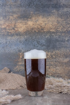 Glass of dark beer with ears of wheat on marble table. high quality photo Free Photo