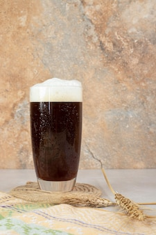 Glass of dark beer with ears of wheat