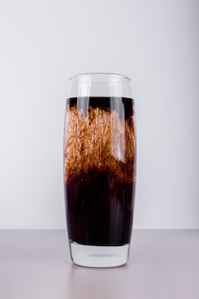 A glass of dark cocktail.