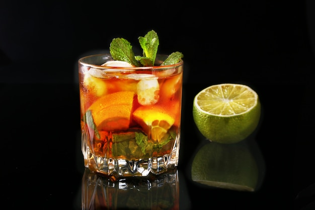 Glass of dark rum cocktail with lime, orange, ice cubes and mint leaves on black mirror background.