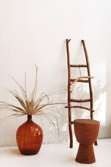 Стеклянная темная ваза с сухими растениями и старинная деревянная лестница с вешалками на белой стене