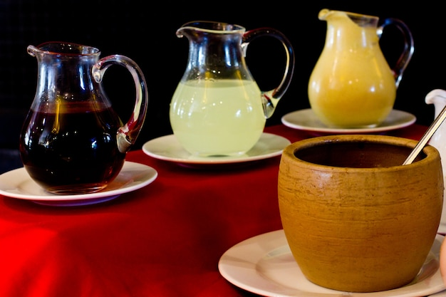 Glass decanters with pomegranate sauce, lemon sauce and mustard. clay yellow pot