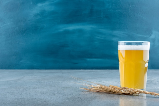 A glass of delicious beer and wheat on gray background. high quality photo