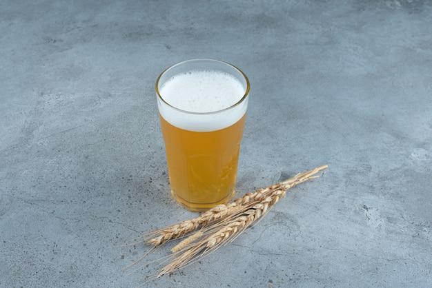 Un bicchiere di deliziosa birra e grano su sfondo grigio. foto di alta qualità