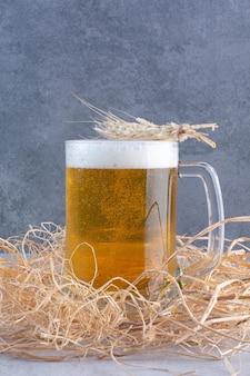 Un bicchiere di birra deliziosa con grano sulla superficie del fieno