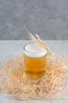 A glass of delicious beer with wheat on hay.
