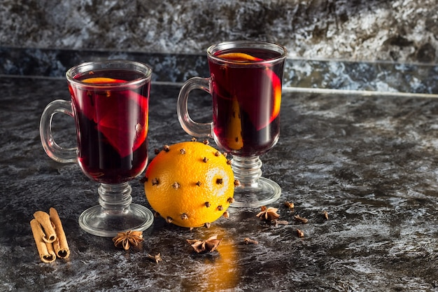 Glass of delicious mulled wine with oranges anise cinnamon on dark table with copyspace