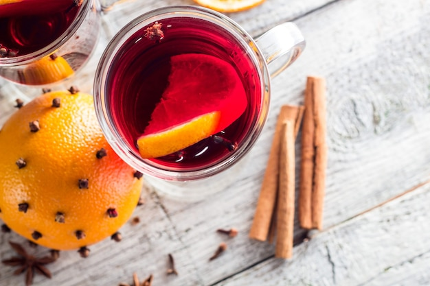 Glass of delicious mulled wine with oranges anise cinnamon on white wooden table with copyspace