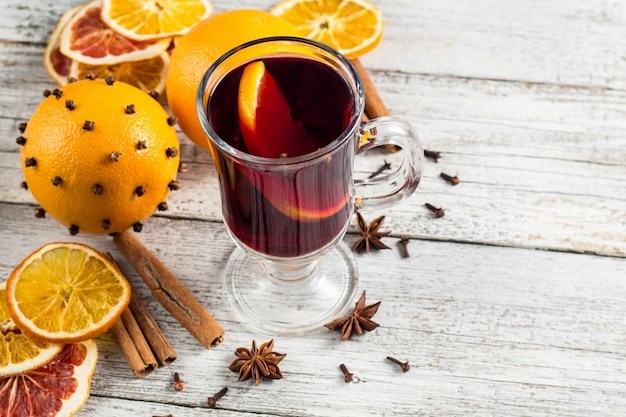Glass of delicious mulled wine with oranges anise cinnamon on white wooden table