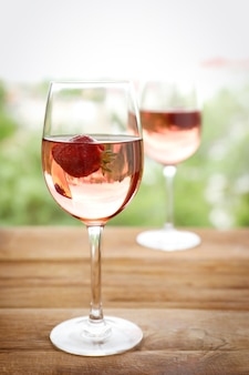Glass of delicious strawberry wine on blurred surface