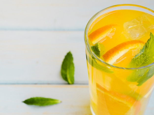Glass of dewy orange juice with slices and mint