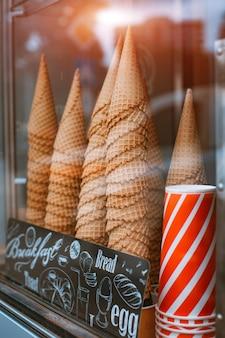 アイスクリームコルネット用の多くのコーンを備えたアイスクリームパーラーコーンのガラス陳列ケース。ヒートストリートのファーストフードでさわやかな夏の食べ物をテイクアウト