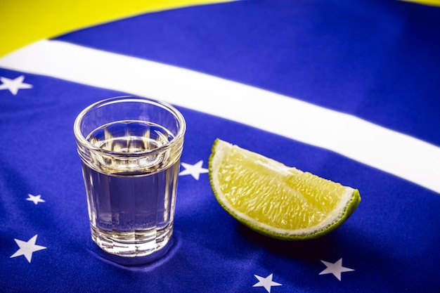 Glass of distilled beverage made from sugar cane, over the brazilian flag, concept of the national