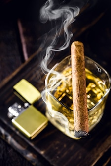 Glass of distilled drink with lit cigar and smoke and lighter