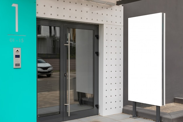 Glass door - entrance to apartment building with blank advertisement banner
