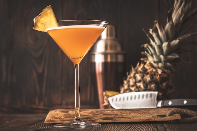 Glass of downhill racer cocktail garnished with pineapple wedge