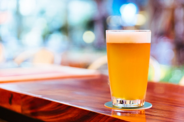 A glass of draft beer with foam on wooden counter with blur and bokeh background.
