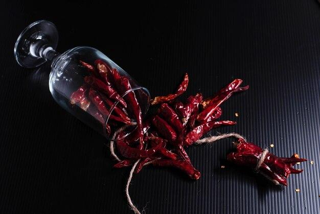 Glass of dried pepper put on black board